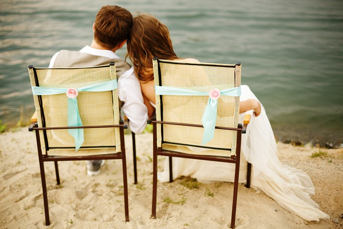 Romantic young newlyweds couple sitting near water on the beach resting after wedding ceremony. Back view of a couple.